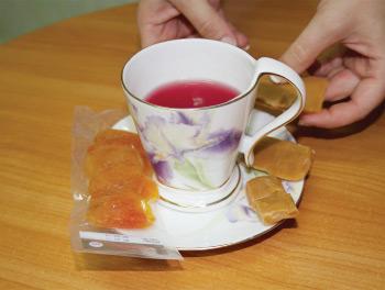 Выдавливаем из тюбика в стакан вишнево-яблочный сок. Выкладываем ирис и курагу.