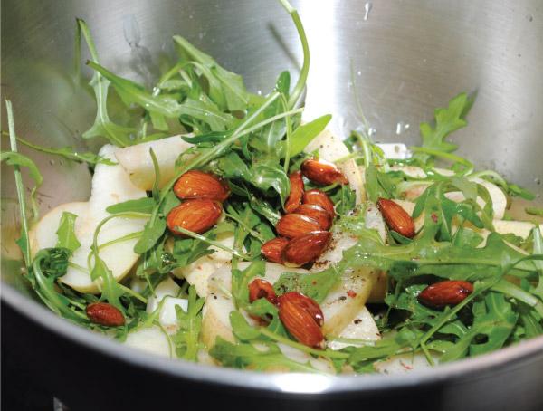 Высыпаем груши в тарелку. Добавляем мяту и рукколу. Заправляем салат оливковым маслом, медом с миндалем. Свежемолотый черный пе-рец — по вкусу.